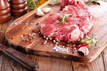 Raw sirloin steak with rosemary and spices on cutting board