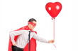 Man in superhero costume holding a balloon