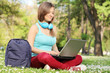 Woman studying with laptop seated in park