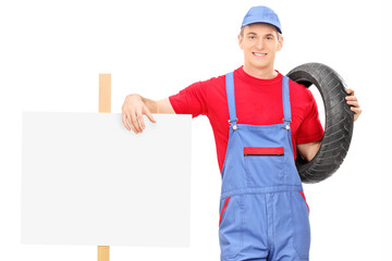 Male mechanic standing next to a blank sign