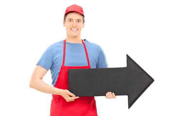 Man in apron holding a big arrow pointing right