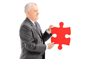Mature businessperson holding a piece of puzzle