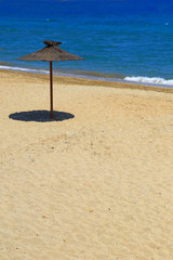Wooden beach umbrella on sandy beach