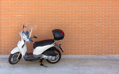 White Motor Scooter against a Brick Wall