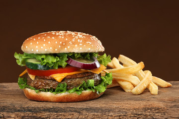 Tasty hamburger and french frites on wood background.