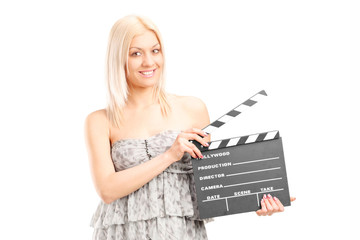 Woman in fashionable dress holding a movie clap