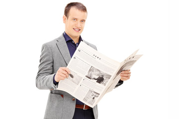 Young man holding a newspaper and looking at camera