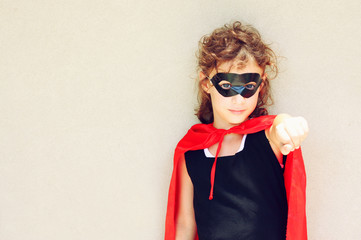 Superhero kid against textured wall background. photographed out