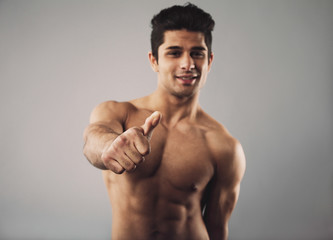 Happy bodybuilder showing thumbs up sign