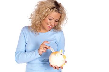 Hübsche lachende junge Frau steck Geld in ihr Sparschwein