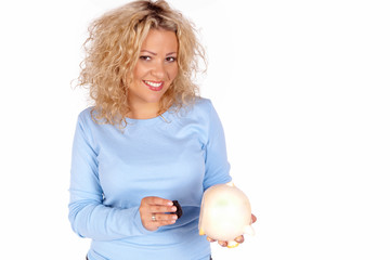 Blonde lachende junge Frau holt Geld aus ihrem Sparschwein