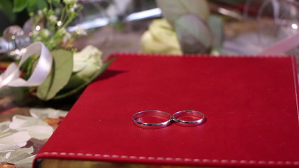 Wedding rings on a red book, surrounded by roses and glasses