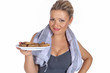 Sportliche Frau mit einem Teller Plätzchen in der Hand