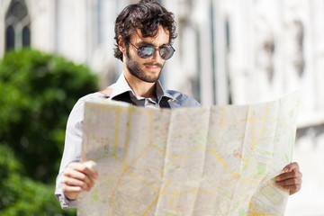 Young turist reading a map in the city