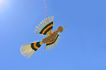 Straw bird flying on a thread against bright blue sky