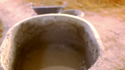 Bucket with concrete and pile of clay. Video shift motion