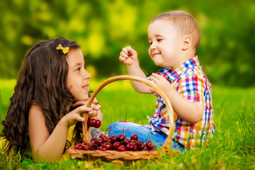 Two fresh tasty cherries in child's hand, outdoors