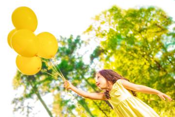 Happy girl with yellow balloons