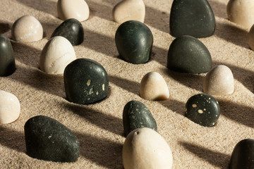 Garden of black and white stones, sticking out of the sand in th