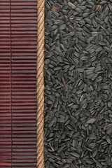 Sunflower seeds  lying on dark bamboo mat, for menu