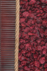 Dried cranberries lying on dark bamboo mat, for menu