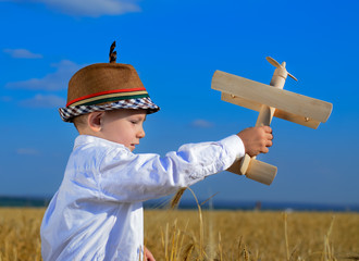 Cute young boy playing with a wooden biplane