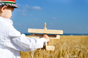 Little boy playing in farmland with a toy airplane