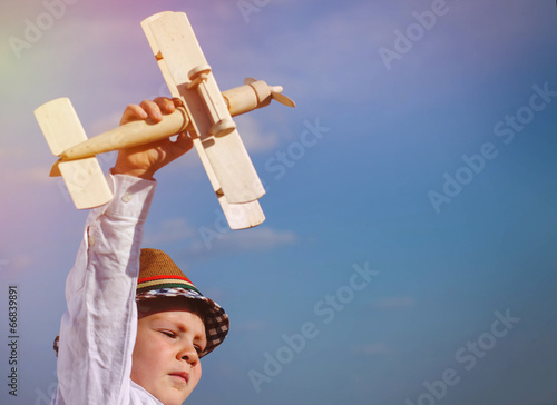 Cute little boy flying his toy biplane