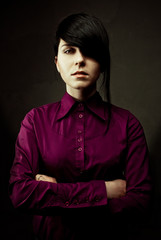girl in darkly violet shirt strictly looks directly in a shot