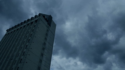 The urban building at the storming clouds background (time