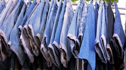 Close up of many blue jeans hanging on a rail.  shift motion