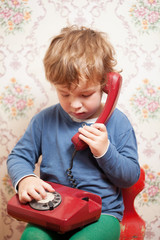 Small boy talking on a red telephone