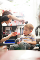 Little boy having a hair cut in a salon