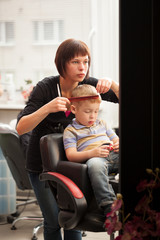 Little boy getting a haircut from hairdresser