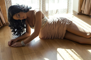 sexy woman in luxurious dress lying on wood floor
