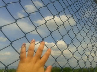 Hand on metal wire close up