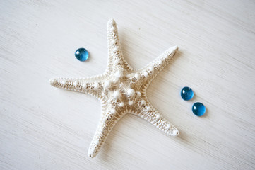 White starfish on a white wooden background with turquoise drops