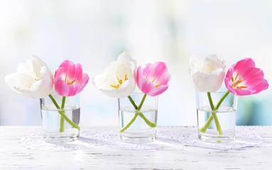 Beautiful tulips in bucket in vase on table on light background