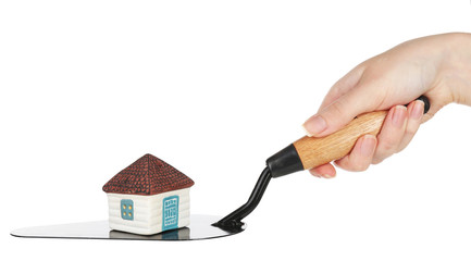 Hand holding wooden toy house on trowel, isolated on white