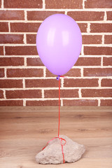 Color balloon with stone on brick wall background