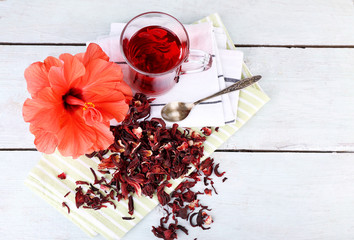 Hibiscus tea and flower on color napkin on wooden background