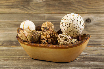 Traditional Wood Ornaments in Wooden Bowl on Rustic Wood