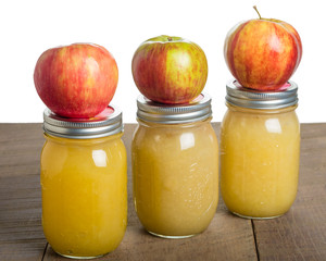 Jars of homemade applesauce with apples