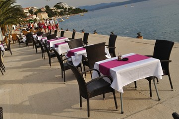 Tables and chairs of restaurant in port of Podgora, Croatia