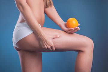 sporty woman holding orange,scin care concept