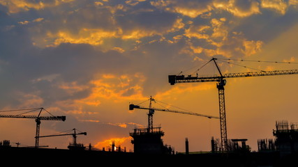 time lapse sunrise and silhouette crane working in construction