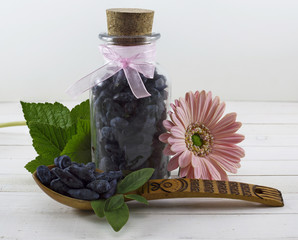 Glass bottle with berries and spoon
