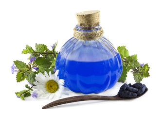 Bottle with blue healing remedy and berries