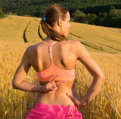 Beautiful runner girl in colorful sport wear in wheat field