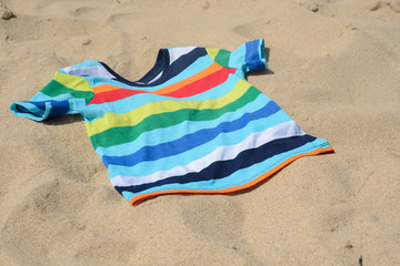 Multicolored child t-shirt on the sand